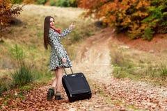 Moça que espera em uma estrada secundária com sua mala de viagem Fotos de Stock Royalty Free