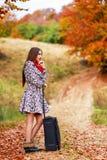 Moça que espera em uma estrada secundária com sua mala de viagem Imagens de Stock