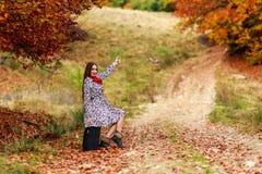 Moça que espera em uma estrada secundária com sua mala de viagem Fotos de Stock