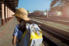 Moça que espera um trem na estação de trem foto de stock