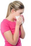 Moça que espirra, sofrendo do frio Imagem de Stock Royalty Free