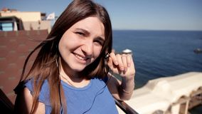 A moça que está em um terraço que negligencia o mar que escuta a música canta e dança video estoque