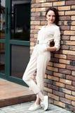 Moça que está na parede de tijolo marrom na rua Foto de Stock