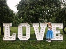 Moça que está nas letras de néon do amor em um parque Fotografia de Stock