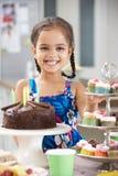 Moça que está pela tabela colocada com alimento da festa de anos imagem de stock