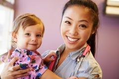 Moça que está sendo guardada pelo doutor pediatra fêmea Imagem de Stock