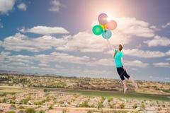 Moça que está sendo levada acima e afastado por balões que é HOL imagem de stock royalty free