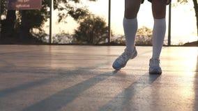 Moça que estica seus pés nas sapatilhas brancas e as peúgas brancas do golfe no campo de básquete local unrecognizable filme