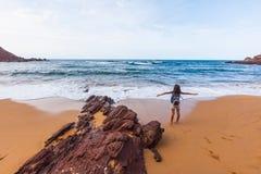 Moça que expressa seu sentimento da liberdade em uma praia vulcânica, Cala del Pilar, ao norte de Minorca, Menorca, Espanha Foto de Stock