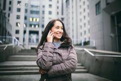 Moça que fala no telefone celular no centro de negócios do pátio a menina com cabelo escuro longo vestiu-se no revestimento do in fotos de stock royalty free