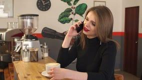 Moça que fala no telefone em uma cafetaria e em um cappuccino quente bebendo video estoque