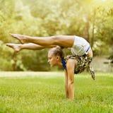 Moça que faz esticando o exercício no verde Foto de Stock Royalty Free