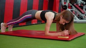 Moça que faz exercícios do Abs para ter uma barriga lisa Mulher muscular bonita que faz o exercício da prancha em um gym para mel video estoque