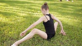 Moça que faz a ioga da ginástica e que estica no parque da cidade no por do sol filme