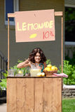 Moça que faz a limonada em seu suporte fotografia de stock royalty free