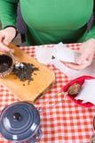 Moça que faz o chá na cozinha Fotografia de Stock
