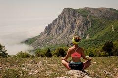 A moça que faz o exercício da aptidão da ioga exterior nas montanhas ajardina Foto de Stock Royalty Free
