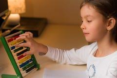 Moça que faz seus trabalhos de casa da escola primária, fim acima Fotos de Stock Royalty Free
