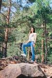 Moça que fica nas rochas da montanha; na parte superior Fotografia de Stock