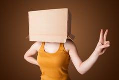 Moça que gesticula com uma caixa de cartão em sua cabeça Fotos de Stock