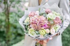 Moça que guarda um ramalhete bonito da mola arranjo de flor com as rosas da hortênsia e do jardim Alvorecer ou por do sol brilhan foto de stock