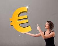 Moça que guarda um sinal grande do euro do ouro 3d Foto de Stock Royalty Free