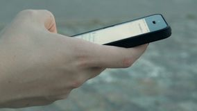 Moça que guarda um telefone celular e ligações através da tela com um dedo video estoque