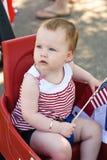 Moça que guarda uma bandeira americana e que monta no vagão vermelho que tem o divertimento no parque para o quarto de julho Fotos de Stock
