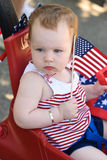 Moça que guarda uma bandeira americana e que monta no vagão vermelho que tem o divertimento no parque para o quarto de julho Imagens de Stock