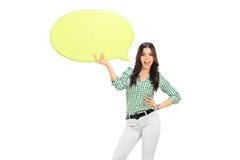 Moça que guarda uma bolha amarela do discurso Fotos de Stock