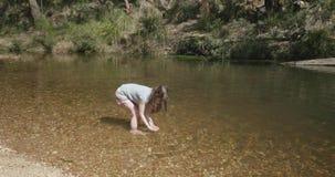 A moça que joga em súbitos de um rio molha em um arco sobre sua cabeça filme