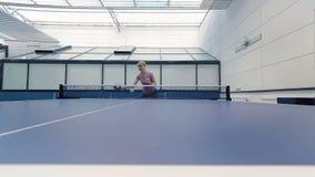 Moça que joga o tênis de mesa na corte vídeos de arquivo
