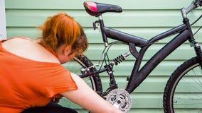 Moça que lava a bicicleta na parede verde filme