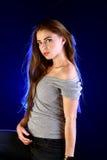 Moça que levanta no fundo azul do luminoso Fotografia de Stock