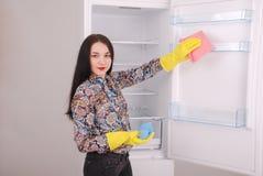 Moça que limpa o refrigerador vazio com uma esponja imagens de stock
