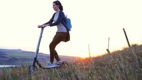 Moça que monta um 'trotinette' bonde em uma montanha no por do sol, mo lento video estoque