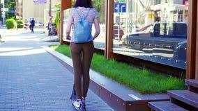 Moça que monta um 'trotinette' bonde na estrada na cidade, vista traseira mo lento video estoque