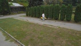 Moça que monta um 'trotinette' no parque Disparado no zangão video estoque