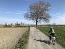 Mo?a que monta uma bicicleta no campo polon?s imagem de stock