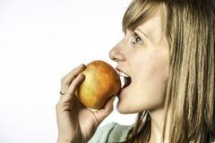 Moça que morde na maçã Fotos de Stock Royalty Free