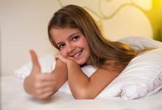 A moça que mostra os polegares levanta o sinal com um sorriso, profundidade rasa Fotos de Stock Royalty Free