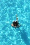 Moça que nada debaixo d'água na claro a água da associação Foto de Stock