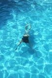 Moça que nada debaixo d'água na claro a água da associação Fotografia de Stock Royalty Free
