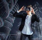A moça que obtém auriculares da experiência VR, está usando monóculos aumentados da realidade, sendo em uma realidade virtual Na  foto de stock