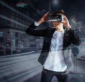 A moça que obtém auriculares da experiência VR, está usando monóculos aumentados da realidade, sendo em uma realidade virtual Na  imagem de stock