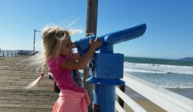 Moça que olha através do telescópio na praia Imagens de Stock