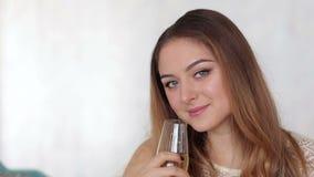 Moça que olha a câmera e que sorri com champanhe à disposição video estoque