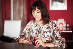 Moça que olha em um telefone Fotos de Stock Royalty Free