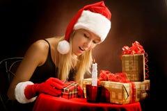 Moça que olha presentes de Natal Imagens de Stock