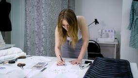 A moça que projeta a roupa nova e que tira esboços no alfaiate compra vídeos de arquivo